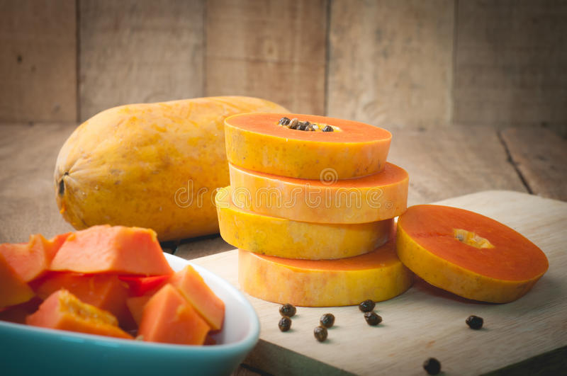 Kitchen table with stack layer slice fresh papaya, papaya seed o. N cutting board - healthy eating and dieting food, concept of health care royalty free stock photo