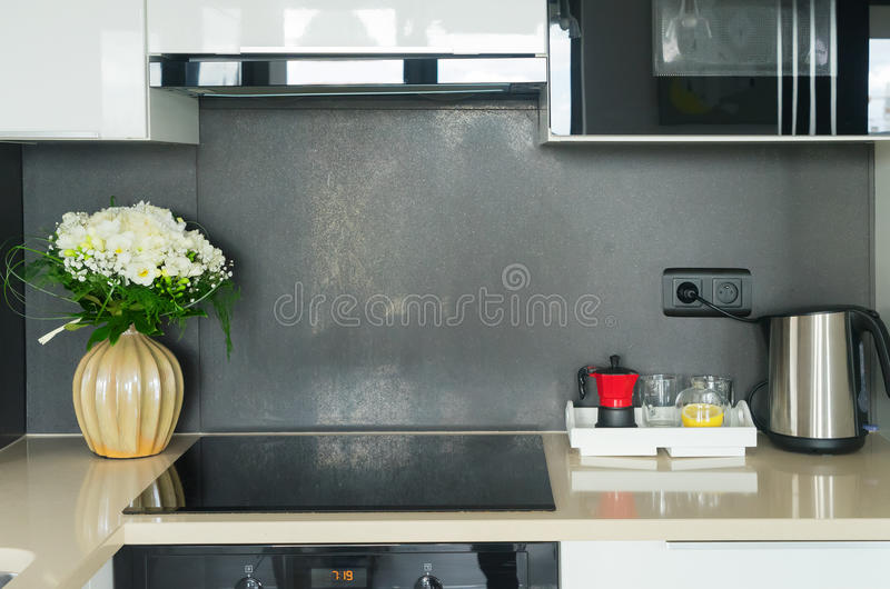 Kitchen table top. With stove, tray with coffee accesoires and flowers stock images