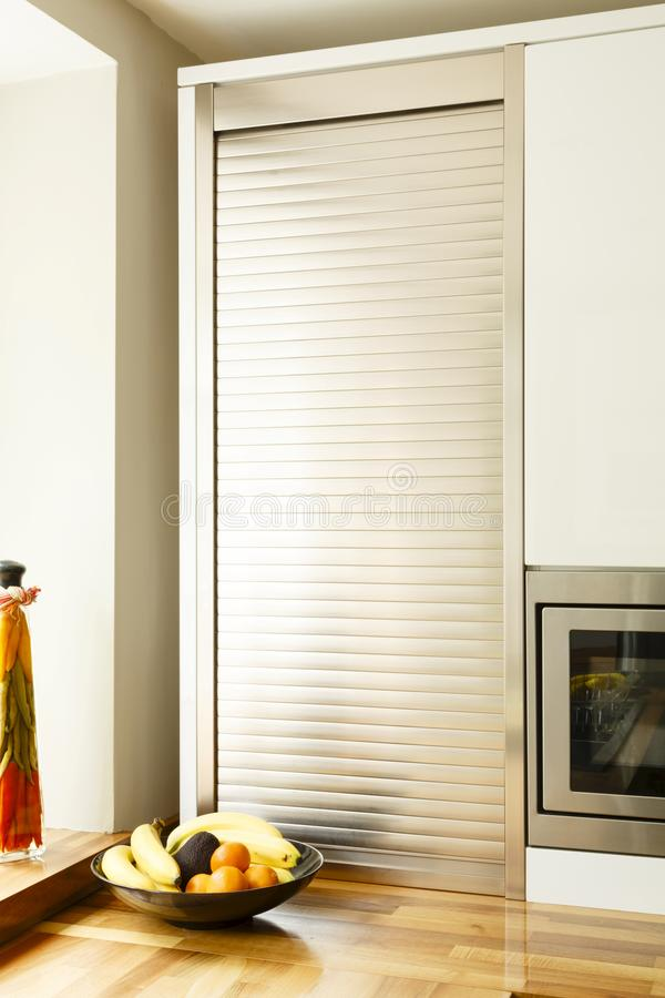Kitchen tambour unit. Modular kitchen with a tambour unit or roller shutter cupboard stock image