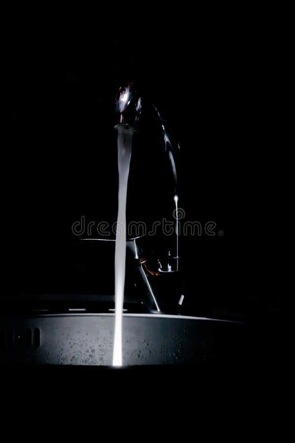 The kitchen tap water flowing glowing royalty free stock photo
