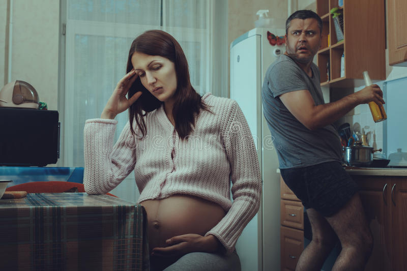 Kitchen is terrible drunk man and a woman sad. stock photos