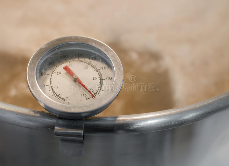 Kitchen thermometer measures the temperature of boiling wort beer homebrew stock images