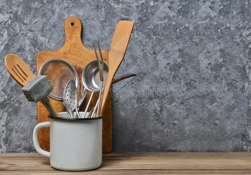 Kitchen tools for cooking on a wooden table on the background of a concrete wall.Copy space. Spoons, forks, wooden spatula stock photos