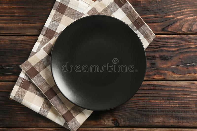 Kitchen towel with plate on wooden background stock image