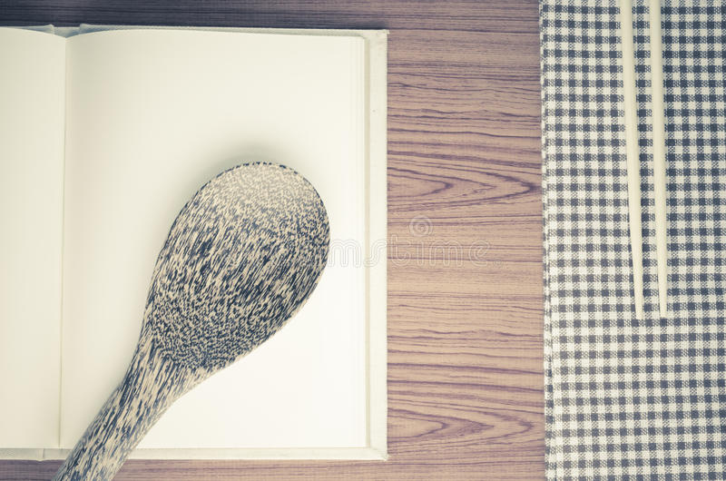 Kitchen towel with spoon on wood background royalty free stock photography