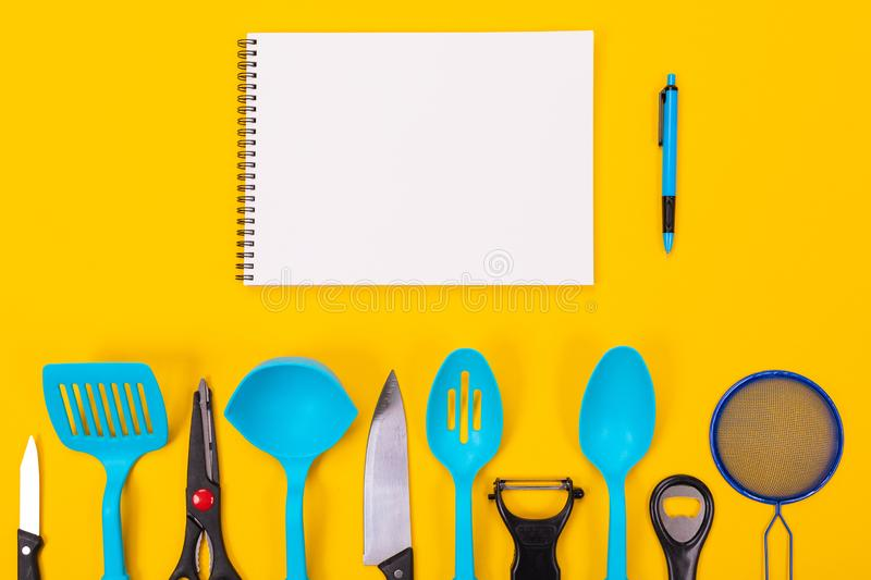 Kitchen utensils and clean sheet of paper isolated on yellow background. Stylish kitchen tools and a clean white sheet of paper in between isolated close-up on a stock photo
