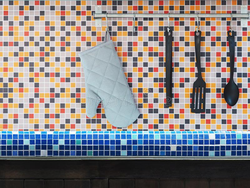 Kitchen utensils hanging over colorful mosaic wall tiles. royalty free stock photos