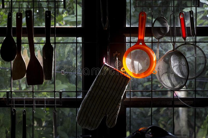 Kitchen utensils hanging on railed windows. A collection of different kitchen utensils are hung at two railed window panes opening to a green garden with bright royalty free stock photography