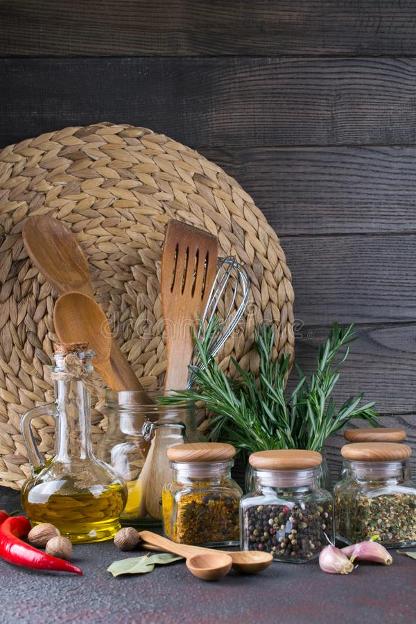 Kitchen utensils, herbs, colorful dry spices in glass jars stock photo