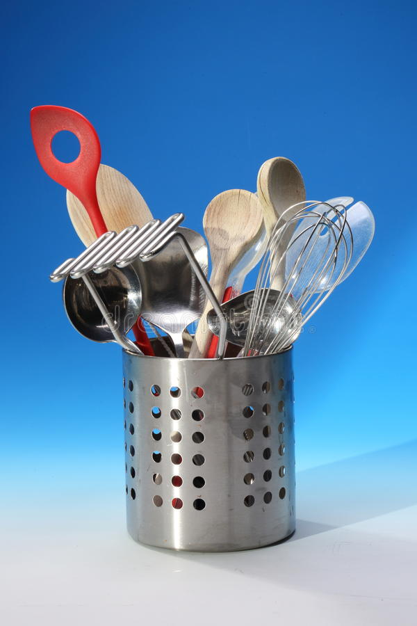 Kitchen Utensils in Metal Holder. Stainless steel container with kitchen tools on a blue background. Whisk, wooden spoons, potato masher, spoons, scoops and stock photos