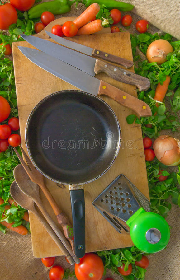 Kitchen utensils - pan, knifes, fork, spoons, grater and wooden surface. Vegetables - carrots, tomatoes, onions and pepper stock photo