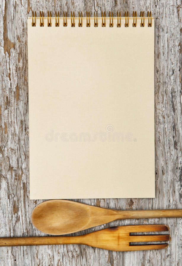 Kitchen utensils and paper spiral notebook on the old wood royalty free stock photography