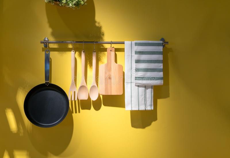 Kitchen utensils and towel hanging on metal rack against yellow. Background royalty free stock photography