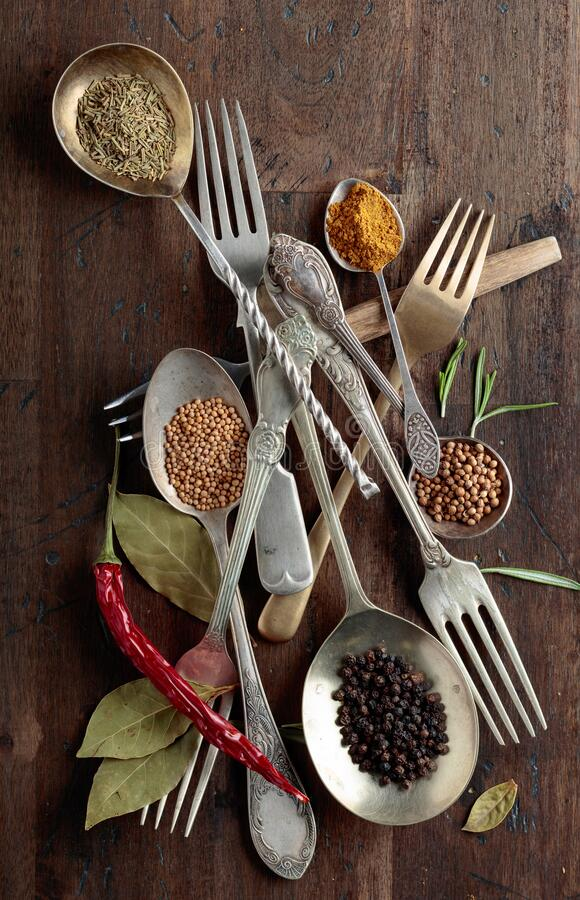 Kitchen utensils with various herbs and spices on wooden table. Top view stock photo