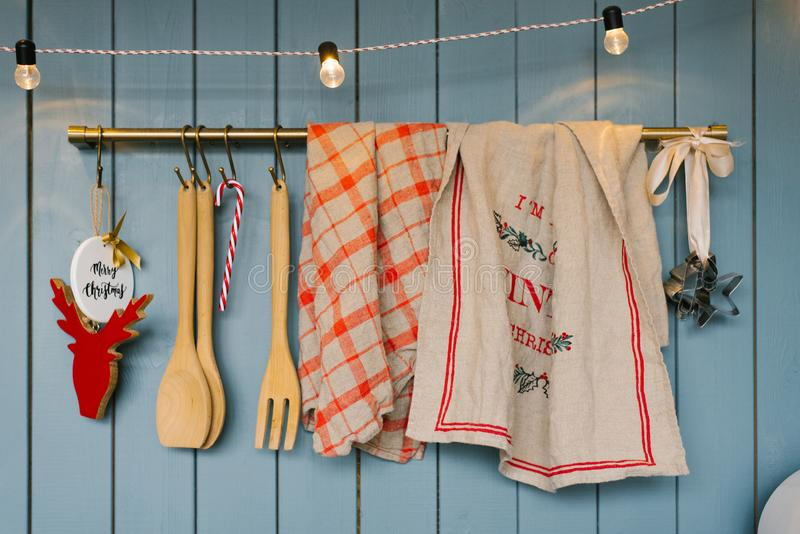 Kitchen utensils: wooden spoons and spatulas, linen towels on the holder in the kitchen in blue tones in Scandinavian style, decor stock image
