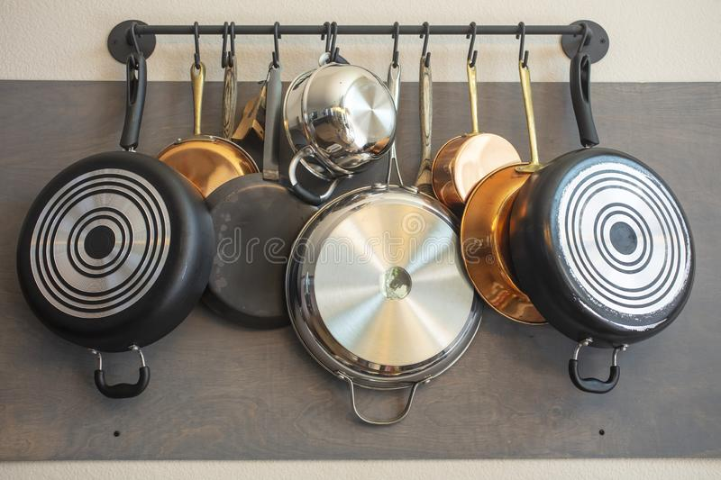 Kitchen wall rack for hanging pots, pans, aprons, and other utensils for storage and decor. Kitchen wall rack for hanging pots, pans, aprons, and other utensils stock photo