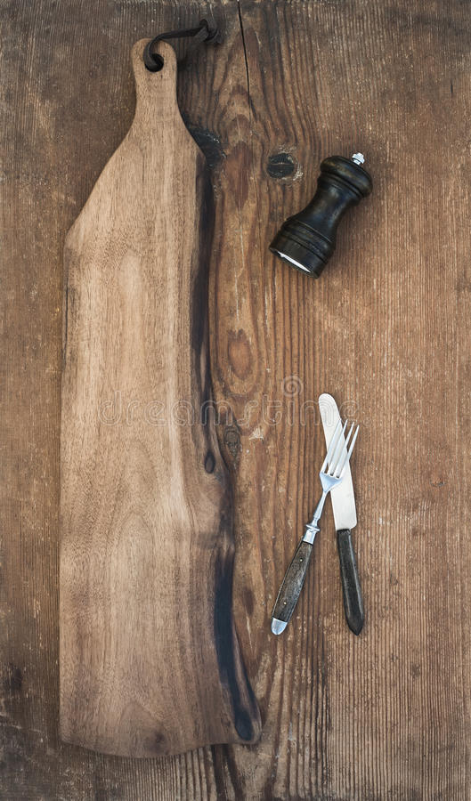 Kitchen-ware set. Old rustic serving board, knive and fork, pepperbox on a old wooden background stock images