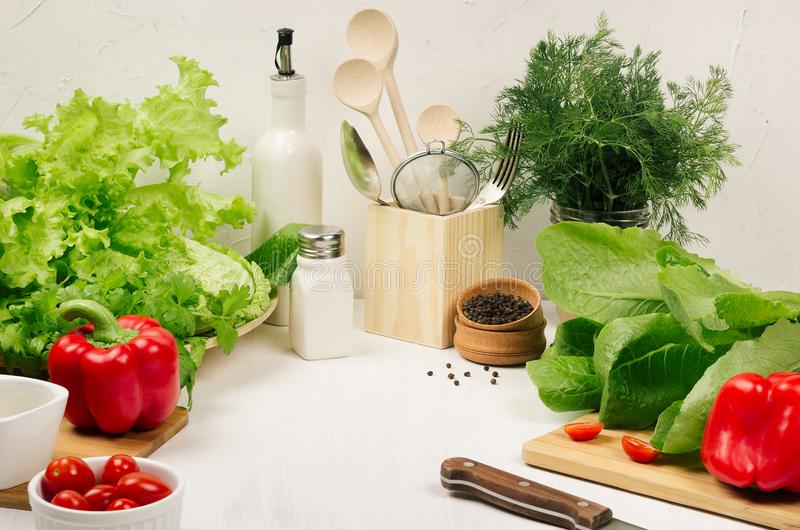 Kitchen white interior with raw fresh green salad, red cherry tomatoes, kitchenware on soft white wood table, copy space. royalty free stock image