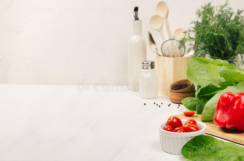 Kitchen white interior with raw fresh green salad, red cherry tomatoes, kitchenware on soft white wood table, copy space. stock photos