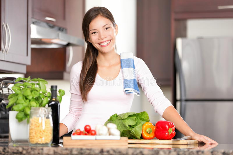 Kitchen woman making food. Kitchen woman making healthy food standing happy smiling in kitchen preparing salad. Beautiful cheerful multicultural Chinese Asian / stock photos