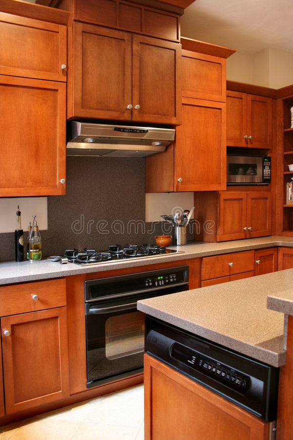 Kitchen wood cabinets black and stainless stove stock images