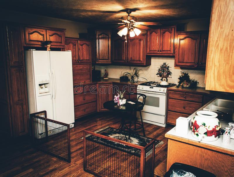 Kitchen With Wood, Wood, and More Wood. Kitchen with a ceiling fan, wood floor, and allot of wood cabinets and drawers along with a white stove and fridge, and royalty free stock image