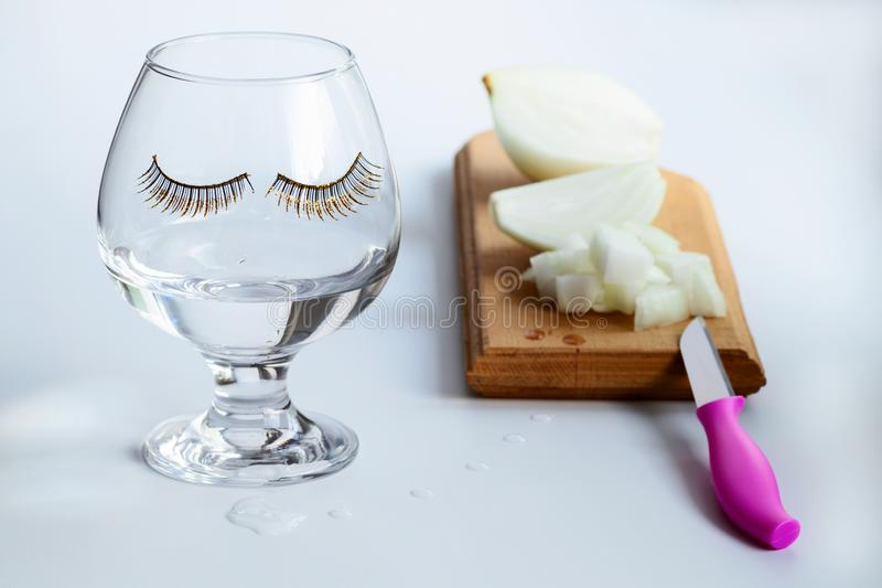 On the kitchen wooden cutting Board cut into pieces burning onions. A glass with applied eyelashes filled with tears from the royalty free stock image