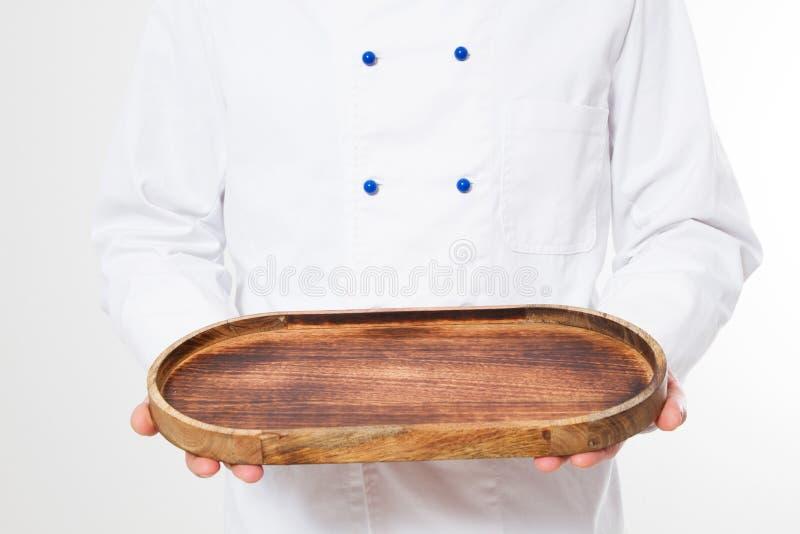 Kitchener, Koch, der leere hölzerne Platte lokalisiert auf weißem Hintergrund mit Kopienraum hält stockbilder
