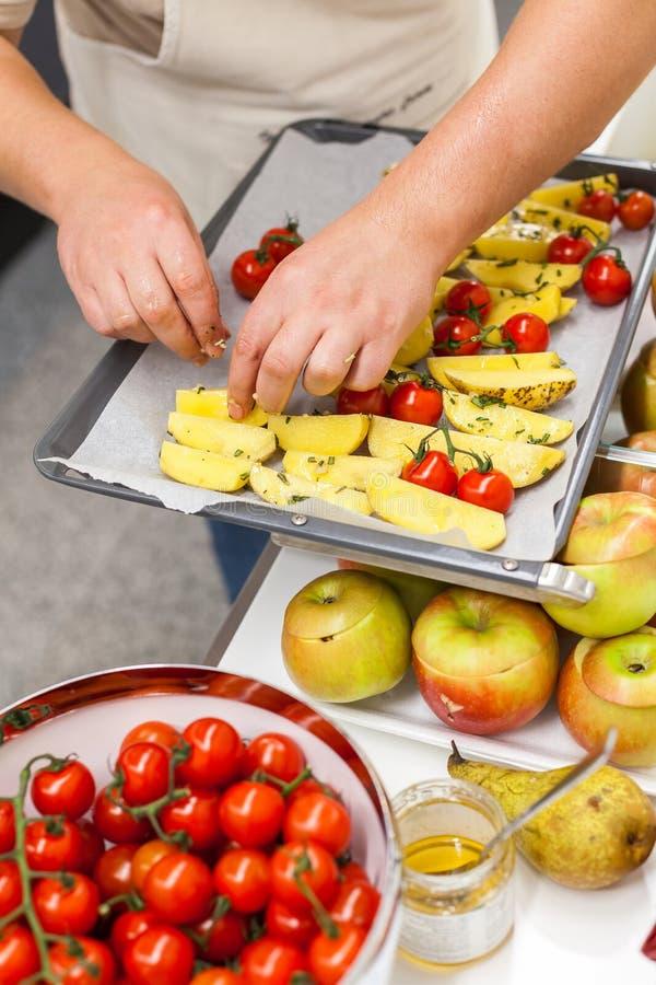 Kitchener setzt Kartoffelscheiben mit frischen Tomaten und Gewürzen auf Wanne stockbild