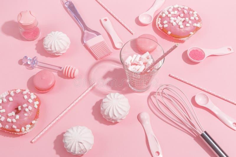 Kitchenware и инструменты, печенье и помадки на розовой предпосылке Взгляд сверху стоковое фото rf