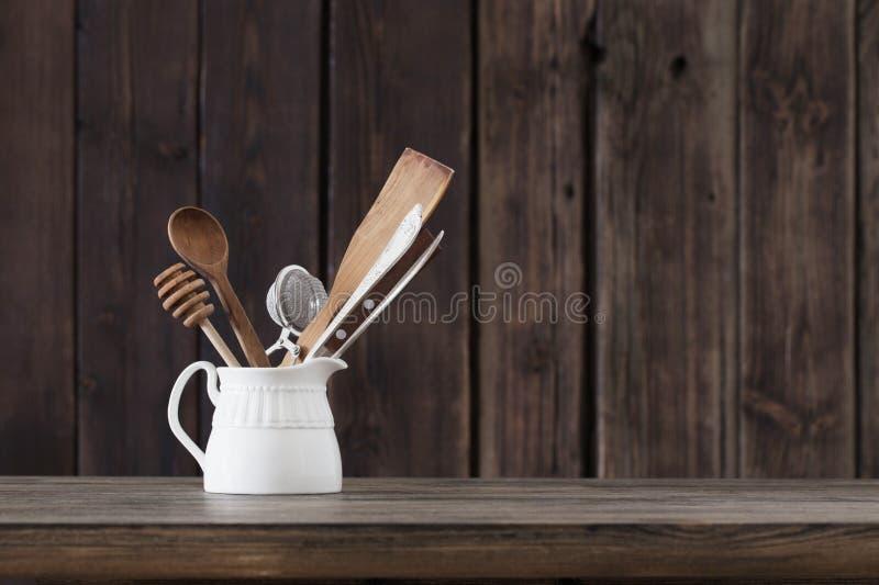 Kitchenware на старой деревянной предпосылке стоковые фото