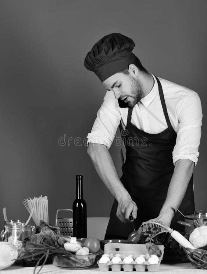 Kitchenware and cooking concept. Chef with attentive face. Holds phone on shoulder and knife on red background. Cook works in kitchen near vegetables and tools royalty free stock photography