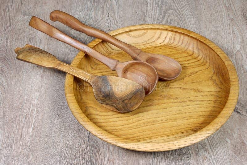 kitchenware cucchiai di legno su un piatto di legno immagine stock