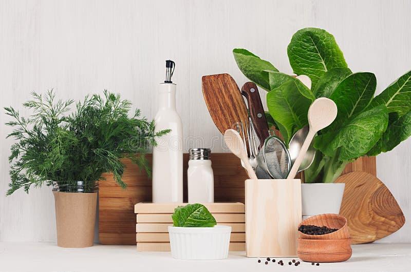 Kitchenware de madeira bege e marrom natural e plantas verdes no fundo de madeira branco claro, espaço da cópia imagens de stock royalty free