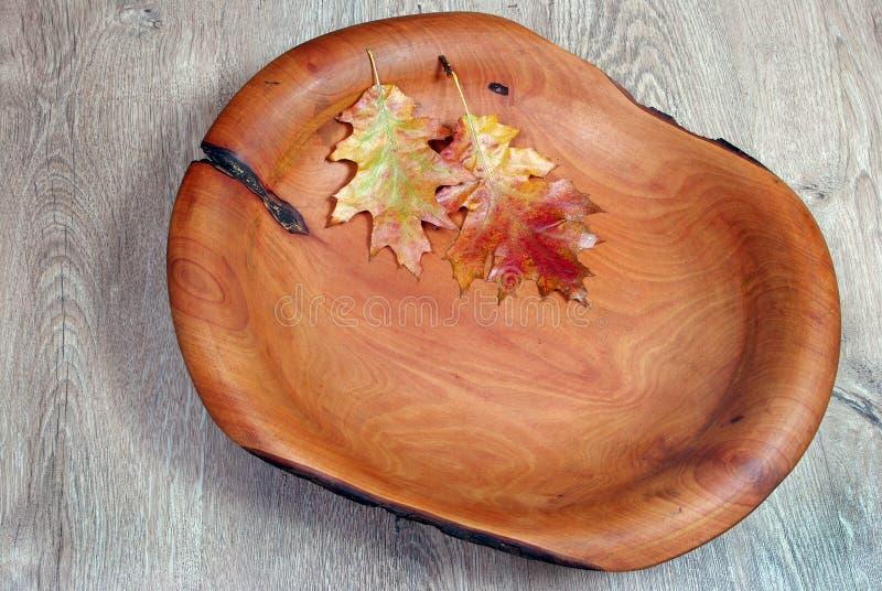 kitchenware Il piatto di legno marrone su un primo piano rustico della tavola immagine stock