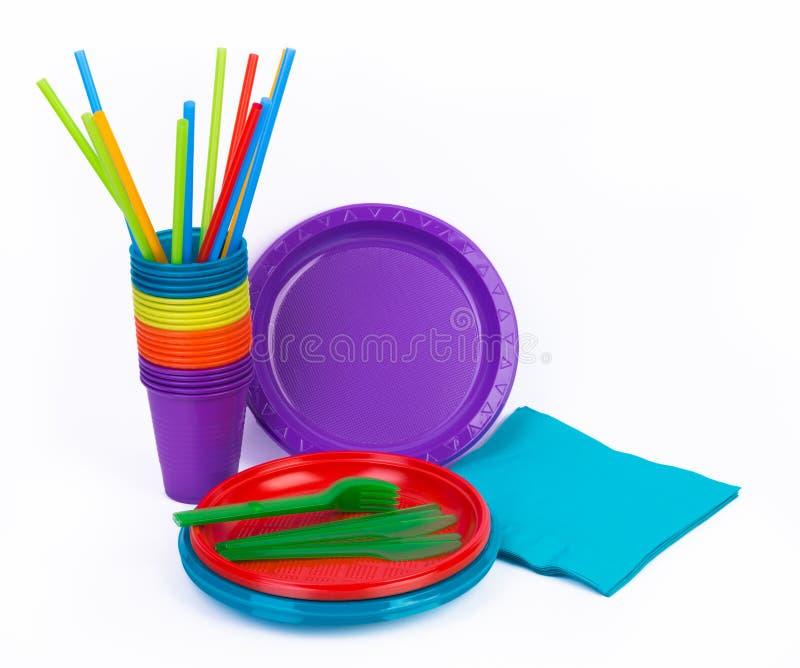 Kitchenware plástico brilhante descartável empilhado no branco foto de stock royalty free