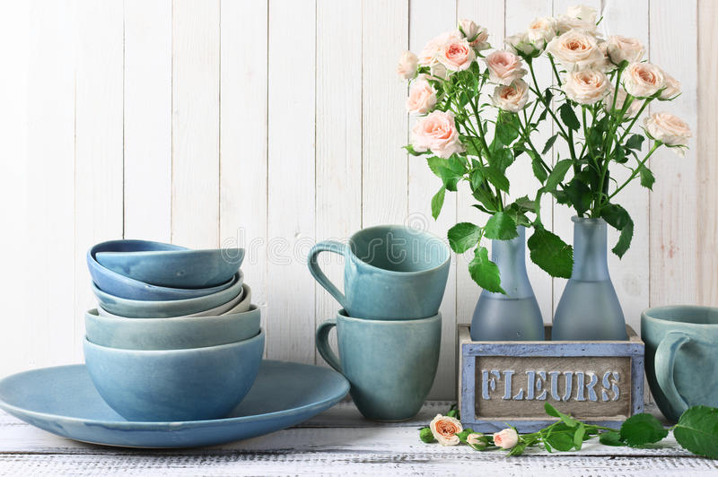 Kitchenware set with roses. Stack of blue handmade ceramic bowls, dish, mugs and pink roses bouquet in rustic vase against white wooden wall royalty free stock image