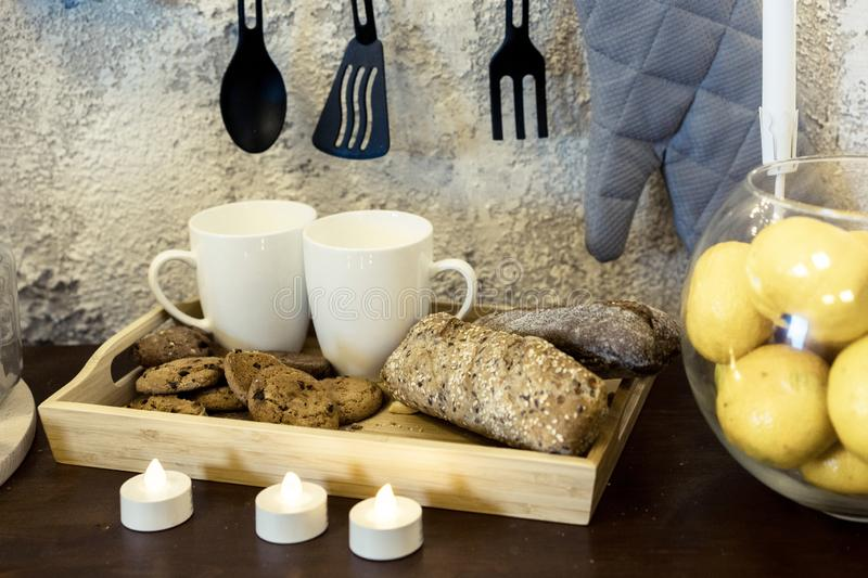 Kitchenware. Two white coffee mugs on a table in front of a concrete wall. Mugs are in a tray with bread. Electric candles. stock photography