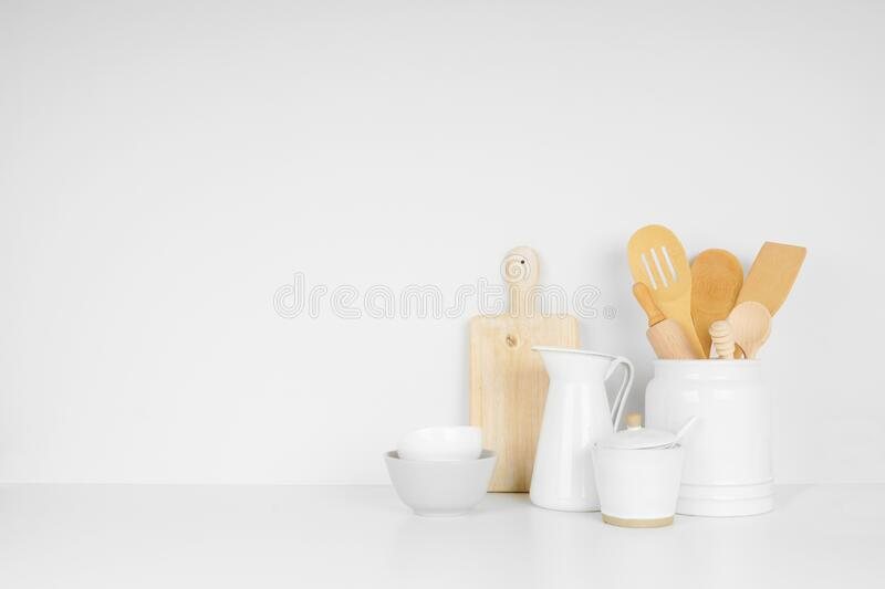 Kitchenware and utensils on a white shelf or counter against a white wall background with copy space. royalty free stock image