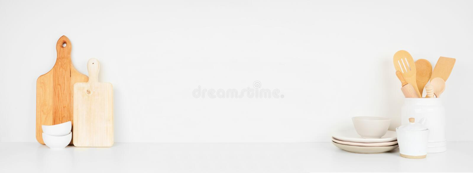 Kitchenware and utensils on a white shelf or counter. Banner with copy space against a white wall. stock photos