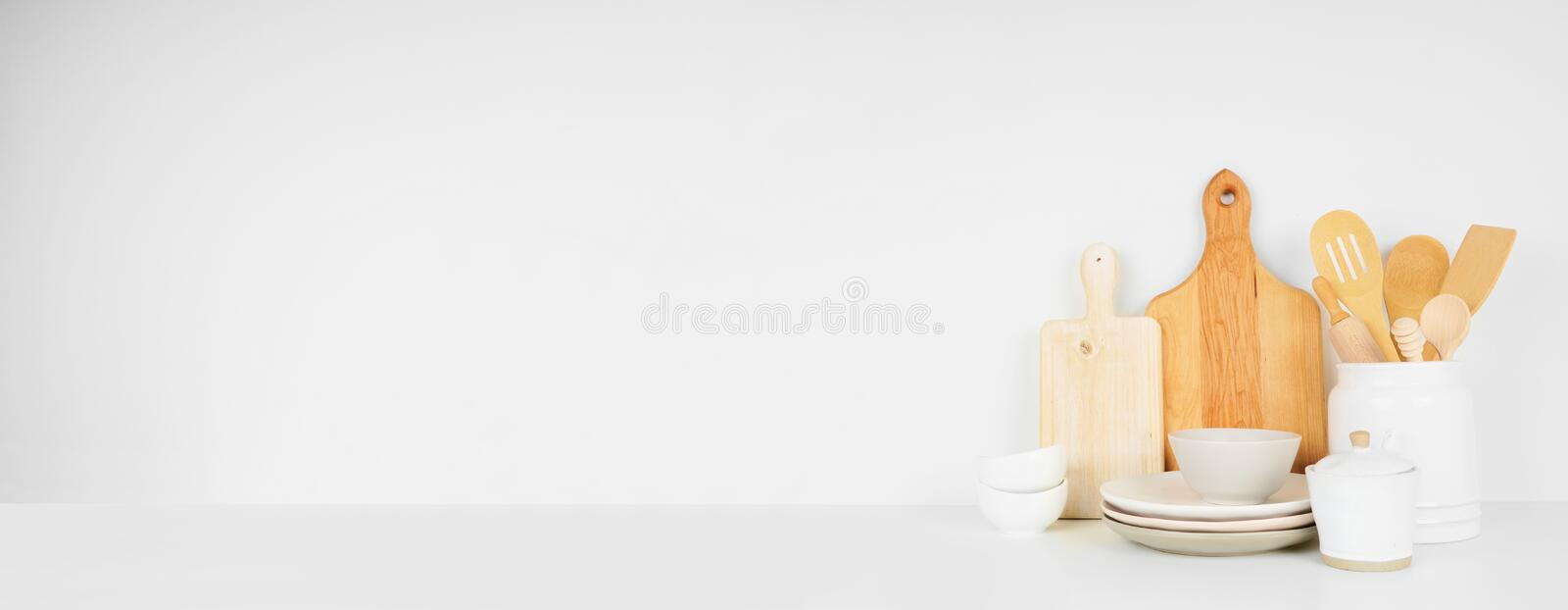 Kitchenware and utensils on a white shelf or counter. Banner with a white wall background and copy space. royalty free stock photography