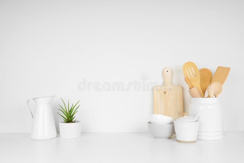 Kitchenware and utensils on a white shelf or countertop with a white wall background and copy space royalty free stock photos