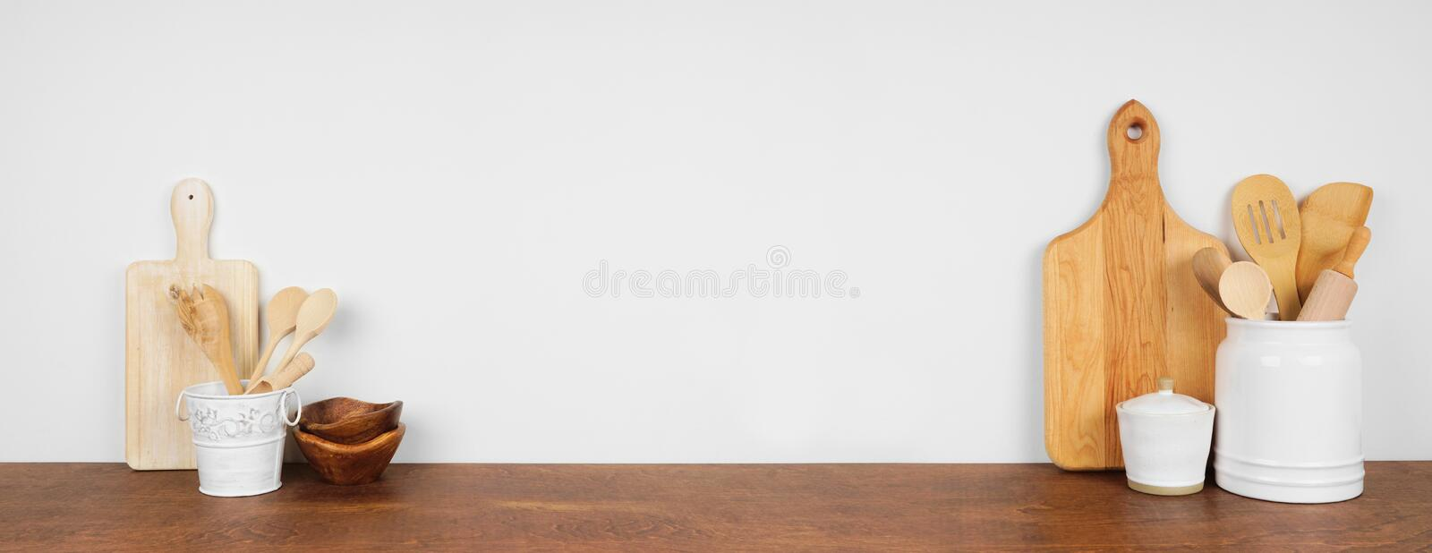 Kitchenware and utensils on a wood shelf or counter. Banner with copy space against a white wall. royalty free stock photo
