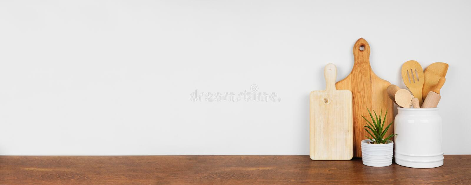 Kitchenware and utensils on a wood shelf. Banner with a white wall background and copy space. stock photos