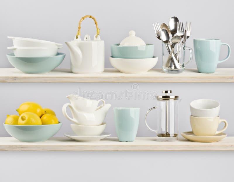 Kitchenware on wooden kitchen shelves stock photos