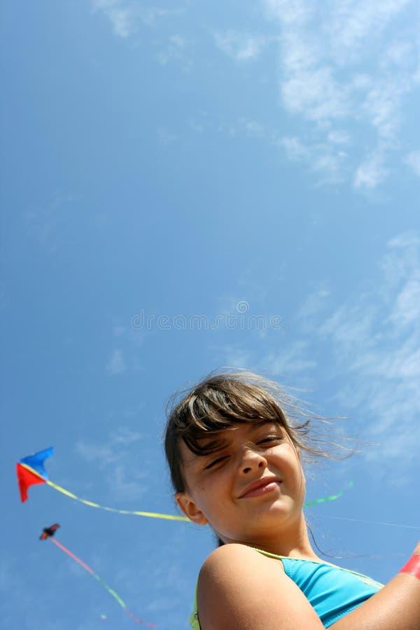 Kite. Girl flying a kite in a beach royalty free stock photos