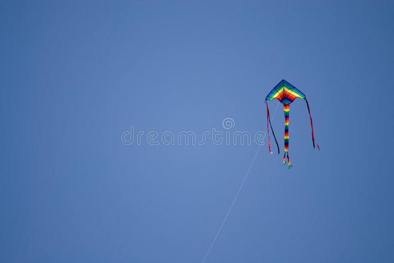 Kite in the air. Kite is flying in the blue sky royalty free stock photo