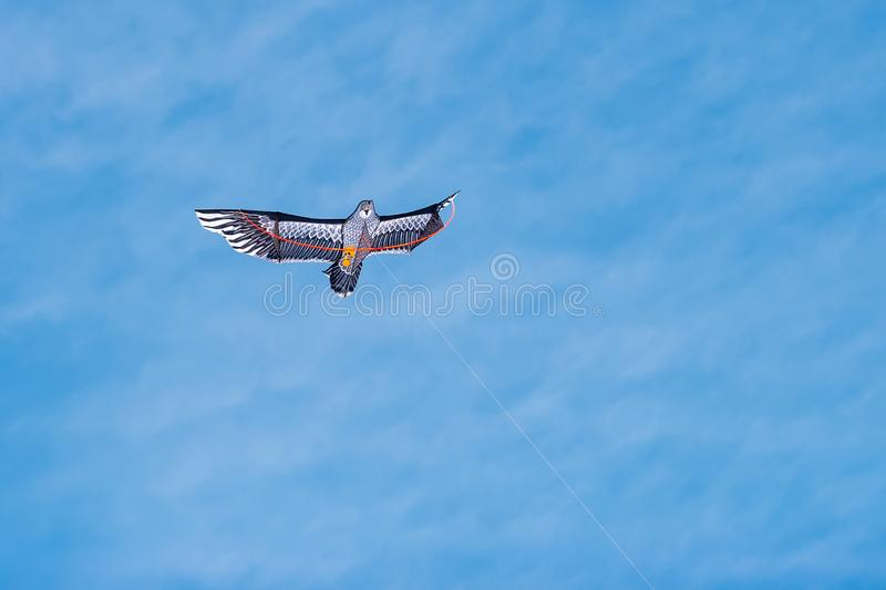 Kite in the blue sky with clouds in the form of an eagle bird. Colored kite on a thread. The wings are open to the sides. Copy space royalty free stock images