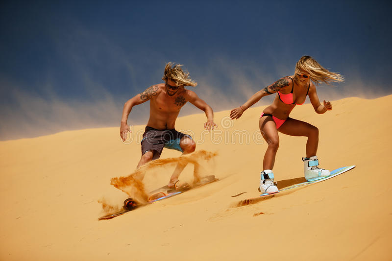 Sand boarding. Couple freestyle at sunset stock image