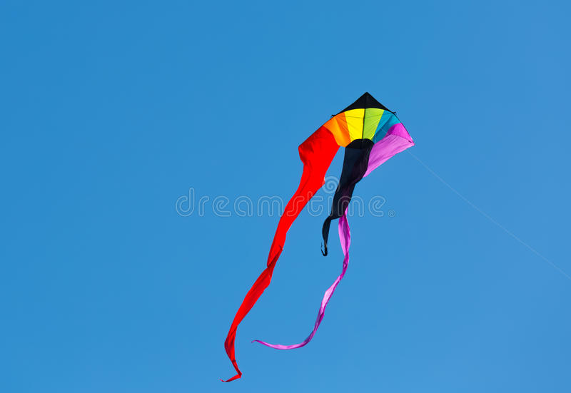 Kite. A colorful kite flies in a cloudless sky royalty free stock photos